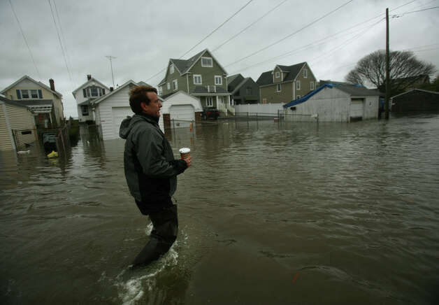 Jay Johnson wades down Melba Street flooded by Hurricane Sandy to check on the condition of his waterfront home in Milford on Monday, October 29, 2012. Photo: Brian A. Pounds / Connecticut Post