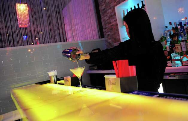 Elaine Chen pours a cocktail on a color-changing bar at Wafu Asian Bistro in Southport, Conn. Photo: Autumn Driscoll / Connecticut Post