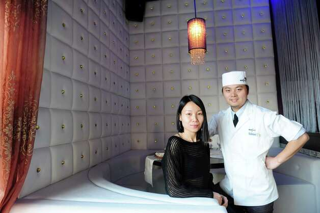 Owners Salmon and Elaine Chen at Wafu Asian Bistro pose in a booth decorated with 200 Swarovski Crystals at their restaurant in Southport, Conn. Photo: Autumn Driscoll / Connecticut Post