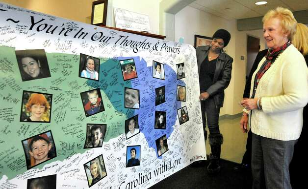 Traci Fant shows a banner honoring the Sandy Hook victims to First Selectman Pat Llodra in Newtown Town Hall Thursday, Jan. 24, 2013. Fant and her husband, Jeff, drove the banner to Newtown from Greenville, S.C. Photo: Michael Duffy / The News-Times