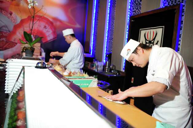 Owner Salmon Chen slices fish for sashimi at Wafu Asian Bistro in Southport, Conn. Photo: Autumn Driscoll / Connecticut Post