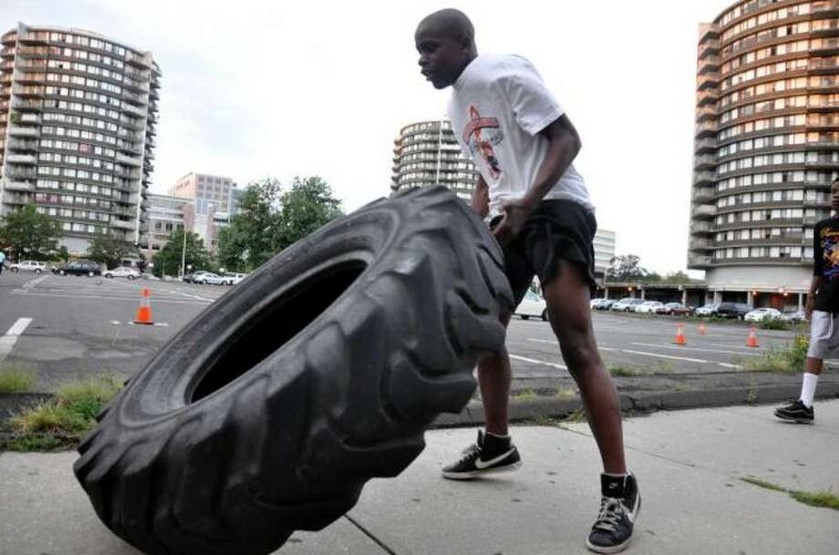 Titus Bruno, 15, of Stamford, flips a tire during a 6 a.m. workout session with fitness instructor Francky Trofort in downtown Stamford, Aug. 22, 2011. Photo: Amy Mortensen