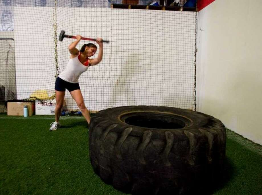 Lisa Antous, of Danbury, uses a sledgehammer on a tractor tire as one of the many workout stations for Anger Management - The Ultimate Fitness Experience in Danbury, July 20, 2011. Photo: Jason Rearick