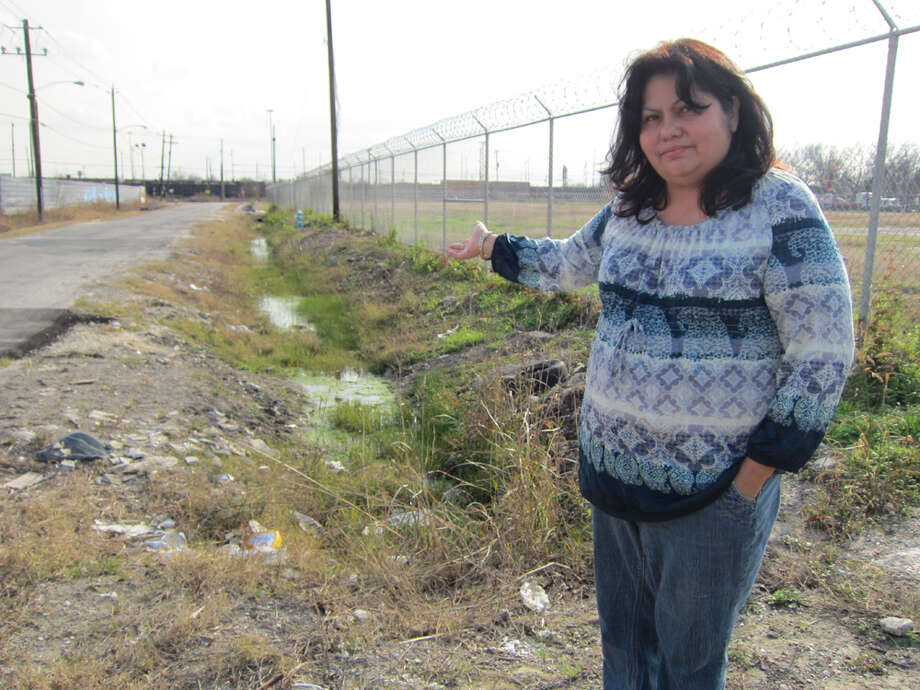 They also dump animals, many of them dead; some still alive. Theresa Armas, 48, points to the ditch where recently someone dumped a dog, alive, chained to a bumper. Photo: Ingrid Lobet / Houston Chronicle