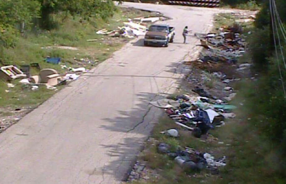 In this image taken from a police video May 7, 2012, a woman lifts a live dog from the back of a Toyota pickup and pitches it into a ditch at an illegal dumpsite in southwest Houston. Image by HPD Photo: Houston Police Dept. / handout