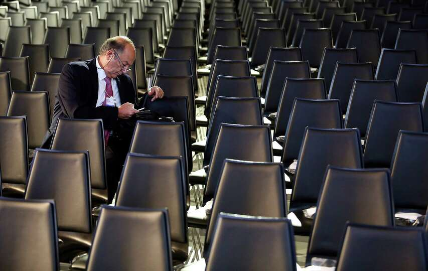 An attendee checks his mobile phone in the main hall of the Congress Center on day two of the World