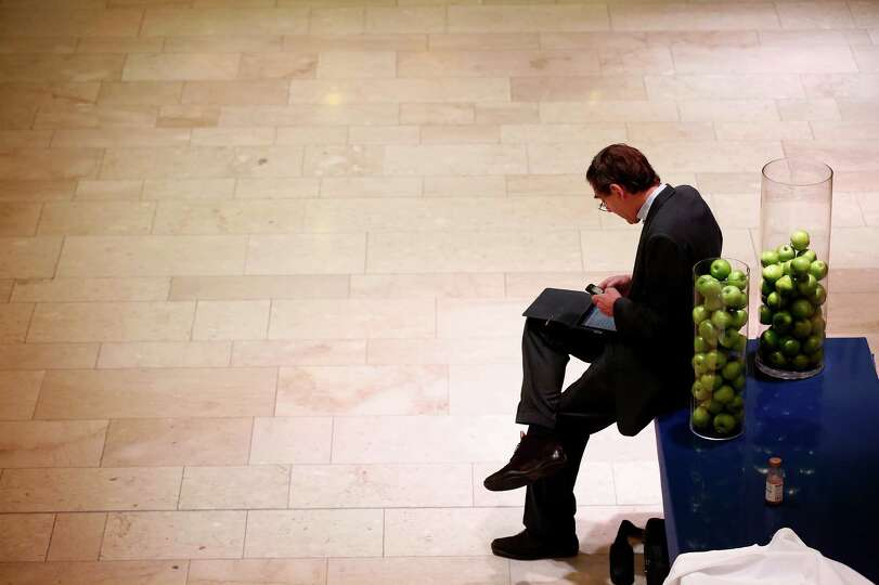 An attendee checks his mobile phone between sessions on day two of the World Economic Forum (WEF) in