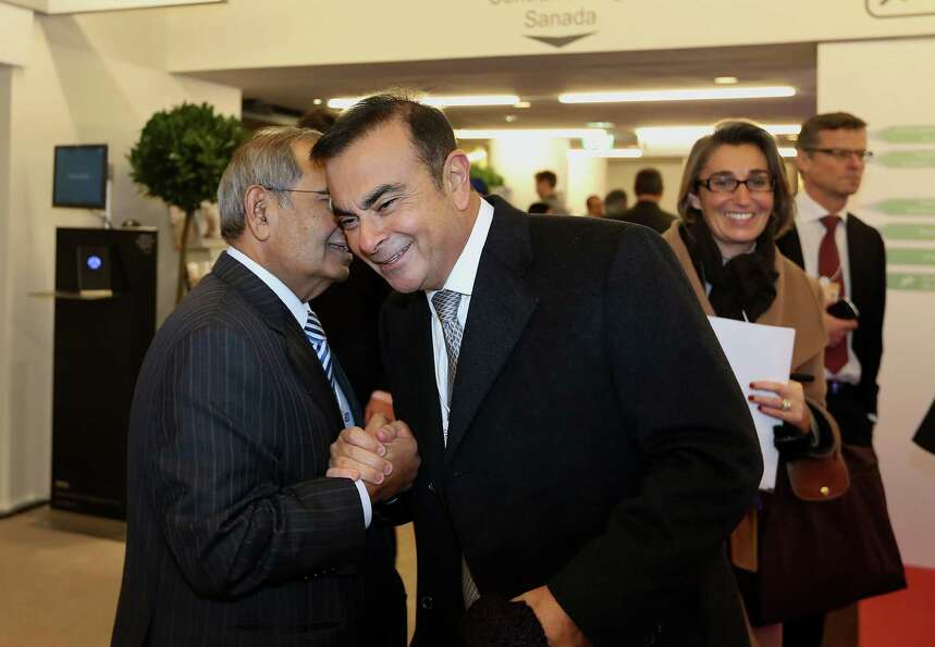 Carlos Ghosn, president and chief executive officer of Nissan Motor Co. Ltd., right, greets a fellow