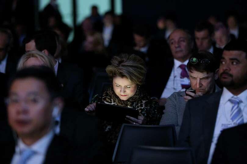 A female member of the audience checks an Apple Inc. iPad ahead of David Cameron, U.K. prime ministe
