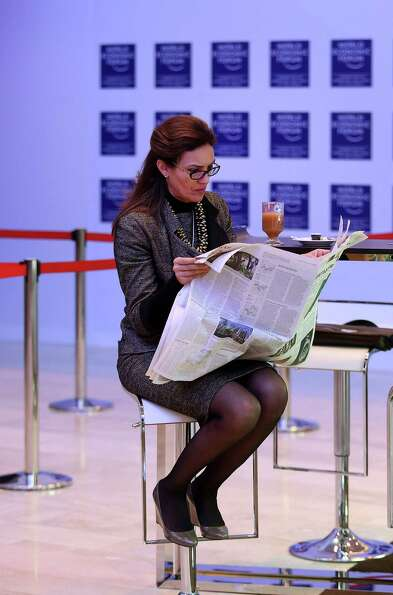 A female attendee reads a newspaper in between sessions on day two of the World Economic Forum (WEF)