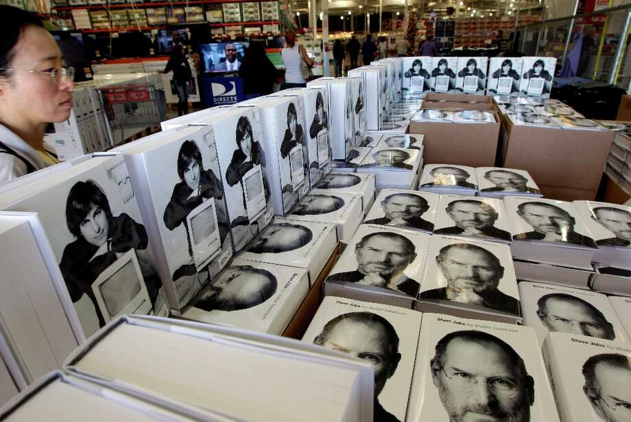 A customer looks at the book Steve Jobs, by Walter Isaacson at a Costco store in Mountain View, Calif., Wednesday, Oct. 26, 2011. Photo: Paul Sakuma, Associated Press / AP