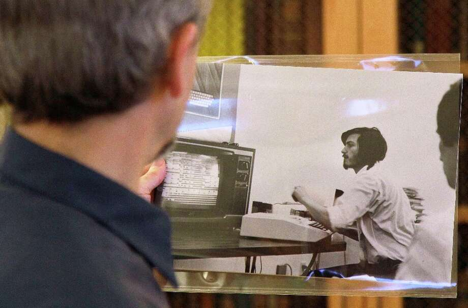 In this photo taken Oct. 25, 2011, curator Henry Lowood is shown looking at an old photograph of Steve Jobs at Stanford's Green Library in Stanford, Calif. Historians and entrepreneurs who want to understand the rise of Apple Inc. and its founder Steve Jobs will find a treasure trove of clues in Stanford University's Silicon Valley Archives. Photo: Jeff Chiu, Associated Press / AP