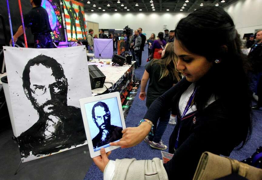 Amy Patel uses her iPad to snap a photo of a portrait of Steve Jobs painted by artist Rick Alonzo at