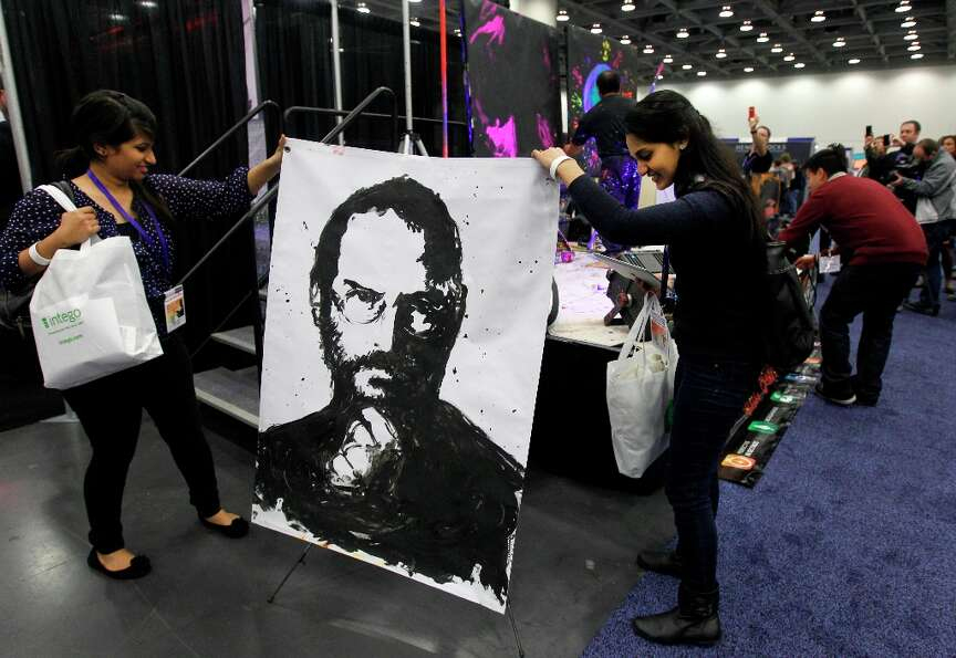 Divya V. (left) and Amy Patel rearrange a portrait of Steve Jobs, painted by artist Rick Alonzo, whi