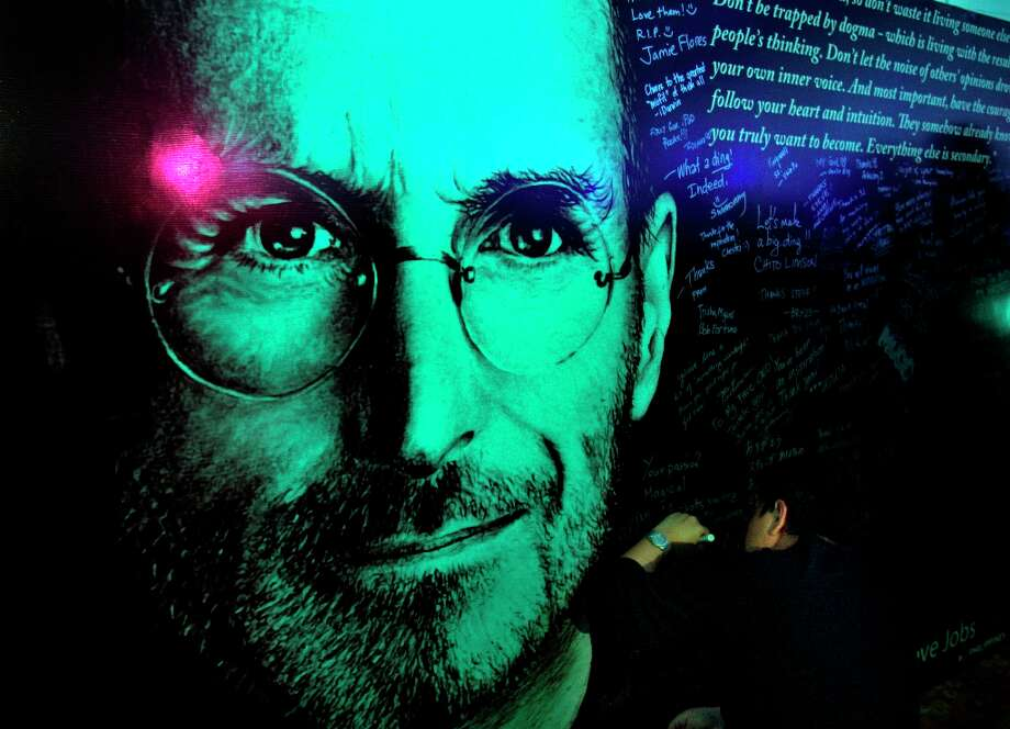 A man writes his message on a board with an image of Steve Jobs in Manila, Philippines, Friday, Oct. 14, 2011. Apple fans called it Steve Jobs Day as a tribute to him. Photo: Pat Roque, Associated Press / AP