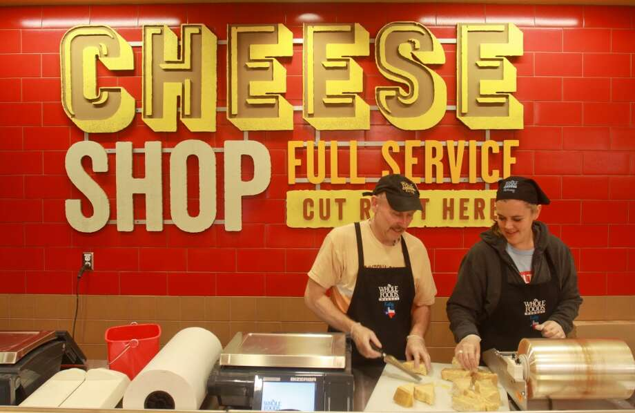Don Gibbs and Jessica Martzke slicing and packaging cheese, in the cheese shop in the new Whole Foods Market in Katy, Jan. 24, 2013.