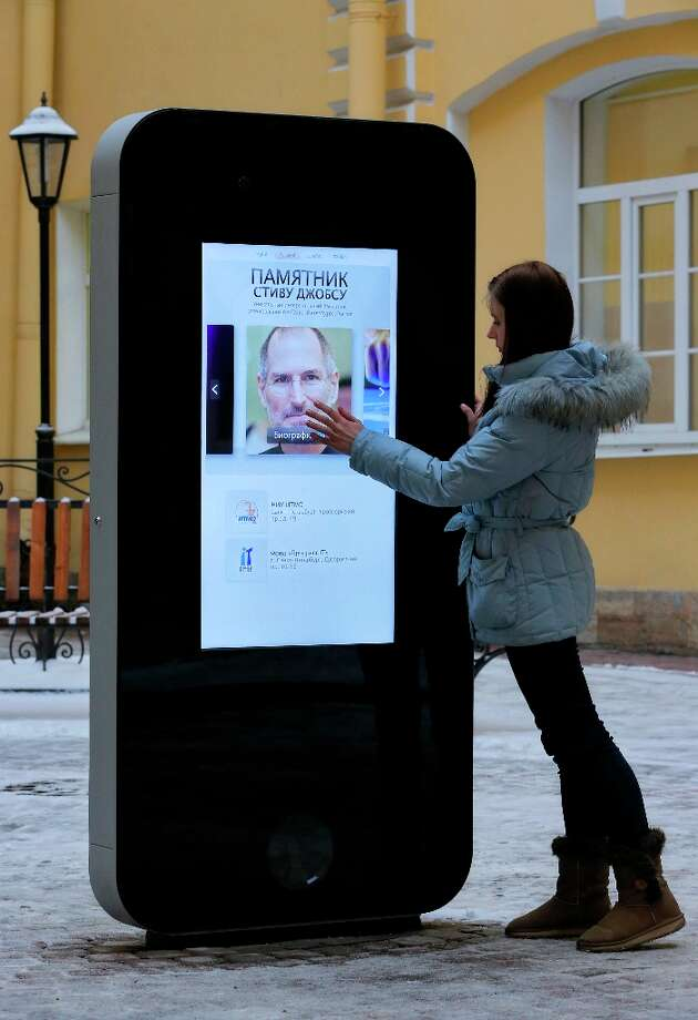 A girl touches the screen showing a portrait of Steve Jobs on the recently erected memorial to the late Apple co-founder in the courtyard of the Techno Park of the St Petersburg National Research University of Information Technologies, Mechanics and Optics (ITMO University) in St. Petersburg, Russia, Thursday, Jan. 10, 2013. The six-foot tall interactive memorial in the shape of a giant iPhone is the first memorial to Steve Jobs in Russia. Photo: Dmitry Lovetsky, Associated Press / AP