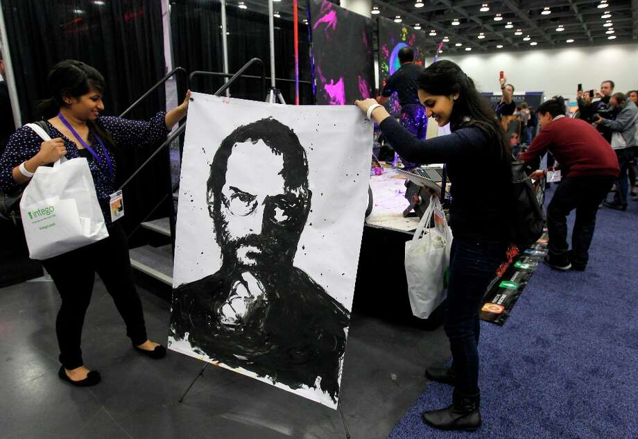 Divya V. (left) and Amy Patel rearrange a portrait of Steve Jobs, painted by artist Rick Alonzo, which fell over at the annual Macworld exhibition in San Francisco, Calif. on Thursday, Jan. 26, 2012. Photo: Paul Chinn, The Chronicle / ONLINE_YES