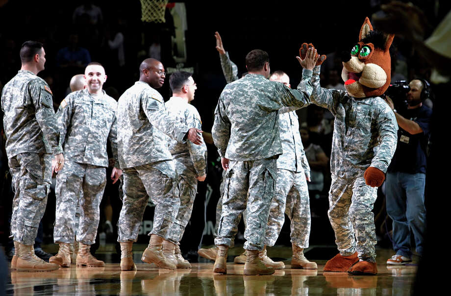 The Spurs Coyote high-fives soldiers who were recognized at the AT&T Center on Nov. 11, 2009. Photo: KIN MAN HUI, San Antonio Express-News / kmhui@express-news.net