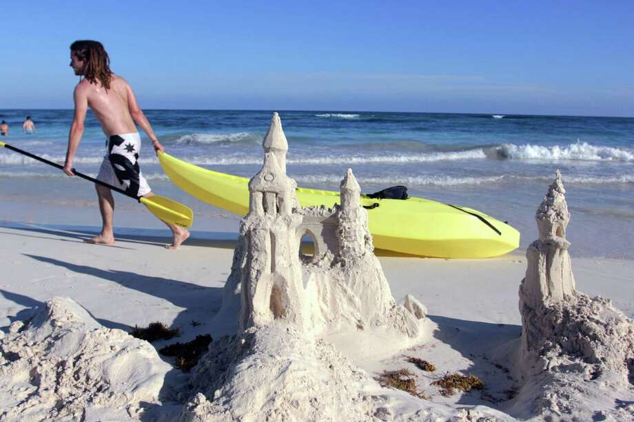 In this Jan. 3, 2013 photograph, a man drags a kayak past a sand castle in Tulum, Mexico. Despite its proximity to Cancun and its fellow party neighbor Playa del Carmen, Tulum is not for the same spring break crowd, attracting a mix of bohemians, well-pocketed New Age types and sun-seekers to its turquoise waters and white sandy beaches. (AP Photos/Manuel Valdes) Photo: MANUEL VALDES / ap
