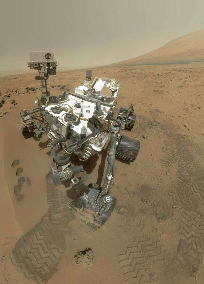 "''High-Resolution Self-Portrait by Curiosity Rover Arm Camera''NASA's Curiosity rover used the Mars Hand Lens Imager to capture this set of 55 high-resolution images, which were stitched together to create this full-color self-portrait. The mosaic shows the rover at ""Rocknest,"" the spot in Gale Crater where the mission's first scoop sampling took place. The base of Gale Crater's 3-mile-high sedimentary mountain, Mount Sharp, rises on the right side of the frame. 