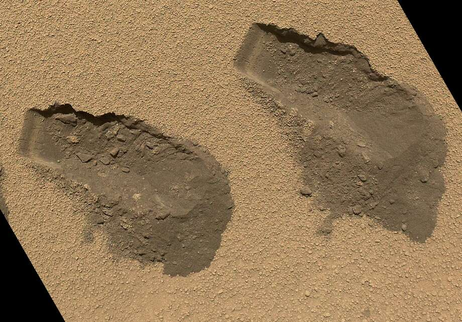 "''Scoop Marks in the Sand at 'Rocknest'''This is a view of the third (left) and fourth (right) trenches made by the 1.6-inch-wide scoop on NASA's Mars rover Curiosity in October 2012. The image was acquired by the Mars Hand Lens Imager and shows some of the details regarding the properties of the ""Rocknest"" wind drift sand. Beneath the crust surface, as revealed in the scoop troughs and the piles of sediment on the right side of each, is finer sand, which is darker brown as compared with the dust on the surface. The left end of each trough wall shows alternating light and dark bands, indicating that the sand inside the drift is not completely uniform. Photo: Caltech/MSSS / NASA/JPL"