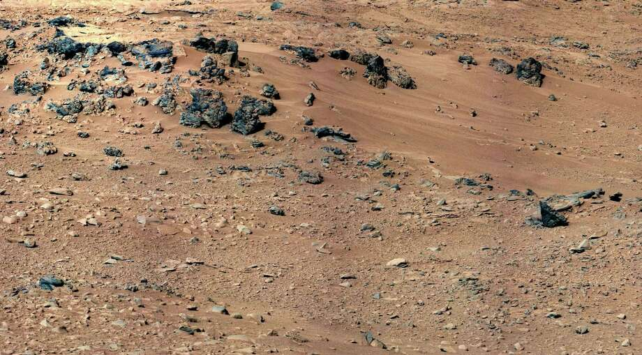 "'''Rocknest' From Sol 52 Location''This patch of windblown sand and dust downhill from a cluster of dark rocks is the ""Rocknest"" site. This view is a mosaic of images taken by the telephoto right-eye camera of the Mast Camera during the 52nd Martian day of the mission. Photo: Caltech/MSSS / NASA/JPL"