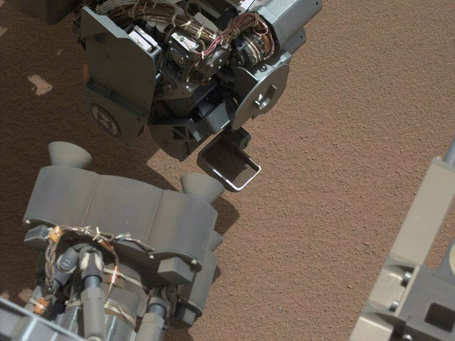 ''View of Curiosity's First Scoop Also Shows Bright Object''This image from the right Mast Camera of NASA's Mars rover Curiosity shows a scoop full of sand and dust lifted by the rover's first use of the scoop on its robotic arm. This image was taken during the mission's 61st Martian day. October 7, 2012. Photo: Caltech/MSSS / NASA/JPL