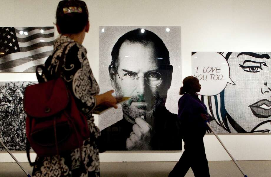 Artist Alex Cao used a mosaic of small images of Neil Armstrong to create an image of Steve Jobs in the DARKE   gallery exhibit booth during the Houston Fine Art Fair in Reliant Center Friday, Sept. 14, 2012, in Houston. Photo: Johnny Hanson, Houston Chronicle / © 2012  Houston Chronicle