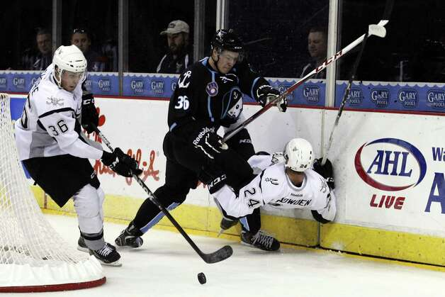 Rampage center Drew Shore (left) takes control of the puck as left wing Quinton Howden falls to the ice while battling Milwaukee's Joonas Jarvinen. Photo by Soobum im//Special to the Express-News Photo: Soobum Im, EN / San Antonio Express-News