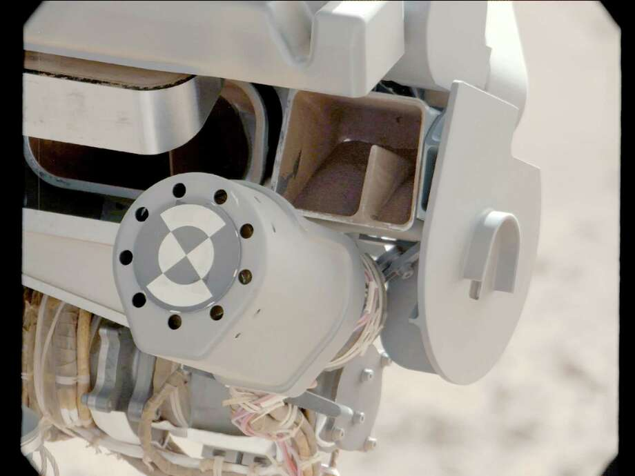 "''Sand Filtered through Curiosity's Sieve''This image shows fine sand from Mars that was filtered by NASA's Curiosity rover as part of its first ""decontamination"" exercise. These particles passed through a sample-processing sieve that is porous only to particles less than 0.006 inches across. The view from the rover's Mast Camera looks into the portion box and ""throat"" of the Collection and Handling for In-Situ Martian Rock Analysis (CHIMRA) tool on the end of the rover's arm. Photo: Caltech/MSSS / NASA/JPL"