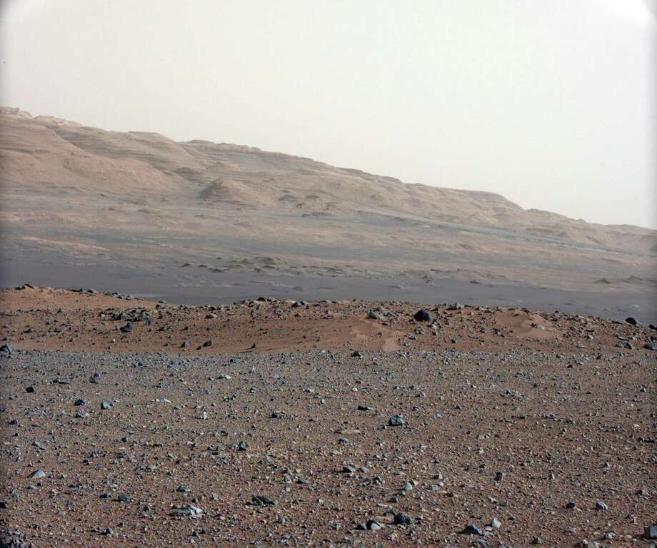 ''Focusing the 34-millimeter Mastcam''This image is from a series of test images to calibrate the 34-millimeter Mast Camera on NASA's Curiosity rover. It was taken on August 23, 2012 and looks south-southwest from the rover's landing site. The gravelly area around Curiosity's landing site is visible in the foreground. Farther away, about a third of the way up from the bottom of the image, the terrain falls off into a depression (a swale). Beyond the swale, in the middle of the image, is the boulder-strewn, red-brown rim of a moderately-sized impact crater. Farther off in the distance, there are dark dunes and then the layered rock at the base of Mount Sharp. Some haze obscures the view, but the top ridge, depicted in this image, is 10 miles away. Photo: Caltech/MSSS / NASA/JPL