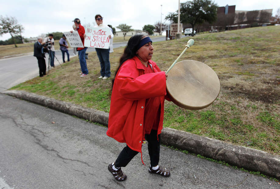 Diane Flores beats a Native American drum as she joins members and supporters of the Texas Indigenous Council in a protest in front of the Catholic Archdiocese of San Antonio on Thursday, Jan. 24, 2013. One of the issues of the protest centers on 15 remains which were unearthed at Mission San Jose this past year. According to council spokesperson Antonio Diaz, the group wanted to be included in a study of the remains but has been met with exclusion instead from the Archdiocese. Photo: Kin Man Hui, San Antonio Express-News / ©2012 San Antonio Express-News