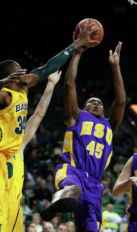 Baylor's Cory Jefferson (34), left, blocks the shot of Hardin-Simmons' JaMael Windom-Haynes (45), in the first half of an NCAA college basketball game, Saturday, Jan. 19, 2013, in Waco, Texas. (AP Photo/Waco Tribune Herald, Rod Aydelotte) Photo: Rod Aydelotte, Associated Press / Waco Tribune Herald