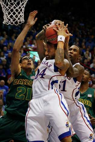 Kansas guard Travis Releford (24) and forward Jamari Traylor (31) rebound against Baylor center Isaiah Austin (21) during the second half of an NCAA college basketball game in Lawrence, Kan., Monday, Jan. 14, 2013. Kansas defeated Baylor 61-44. (AP Photo/Orlin Wagner) Photo: Orlin Wagner, Associated Press / AP