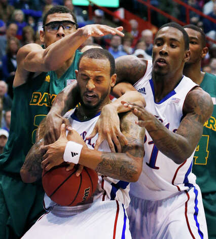 Kansas guard Travis Releford and forward Jamari Traylor (31) work for a rebound against Baylor center Isaiah Austin, left, during the second half of an NCAA college basketball game in Lawrence, Kan., Monday, Jan. 14, 2013. Kansas defeated Baylor 61-44. (AP Photo/Orlin Wagner) Photo: Orlin Wagner, Associated Press / AP