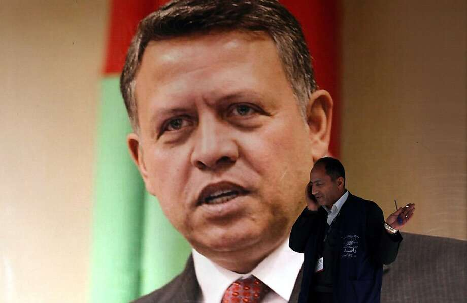 A member of the Jordanian Independent Electoral Commission, walks past a large photograph of King Abdullah II of Jordan, at the counting votes station in Amman, Jordan, Thursday, Jan. 24, 2013. Despite a wide boycott by Jordan's Muslim Brotherhood and other smaller opposition parties, at least three dozen Islamists who ran as independents have won seats in the kingdom's newly empowered parliament, according to initial results released Thursday. (AP Photo/Mohammad Hannon) Photo: Mohammad Hannon, Associated Press