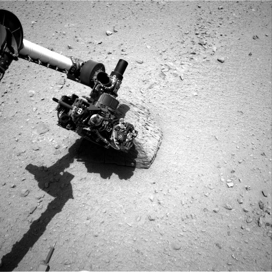 "''Curiosity's Rock-Contact Science Begins''This image shows the robotic arm of NASA's Mars rover Curiosity with the first rock touched by an instrument on the arm. The rover's right Navigation Camera (Navcam) took this image during the 46th Martian day, or sol, of the mission, September 22, 2012. The rover placed the Alpha Particle X-Ray Spectrometer (APXS) instrument onto the rock to assess what chemical elements were present in the rock. The rock is named ""Jake Matijevic"" in commemoration of influential Mars-rover engineer Jacob Matijevic (1947-2012). Photo: Caltech/MSSS / NASA/JPL"