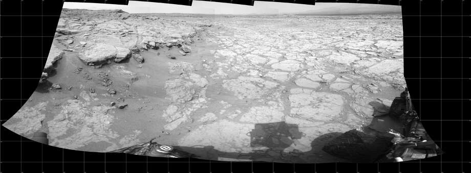 "''At Edge of 'Yellowknife Bay,' Sol 130''In a shallow depression called ""Yellowknife Bay,"" the NASA Mars rover Curiosity drove to an edge of the feature during the 130th Martian day, or sol, of the mission, December 17, 2012, and used its Navigation Camera to record this view of the ledge at the margin and a view across the ""bay.""