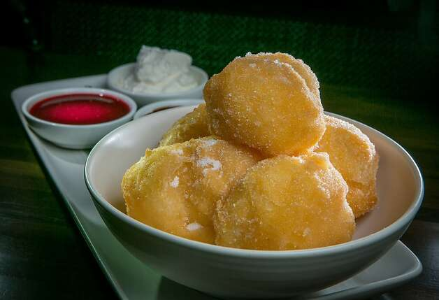 Sugar egg puffs are similar to crisp beignets, and are served with three sauces. Photo: John Storey