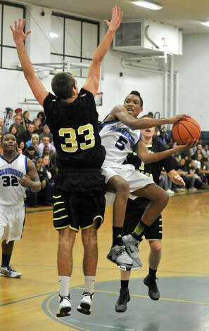 Abbott Tech's Brandon Henry drilves to the basket while under pressure from a leaping Cooper Brown, of Joel Barlow, during their game in the first round of The News-Times Greater Danbury Tip-Off Classic at the Danbury War Memorial on Thursday, Dec. 13, 2012. Joel Barlow advanced to the next round beating Abbott Tech, 67-49. Photo: Jason Rearick / The News-Times