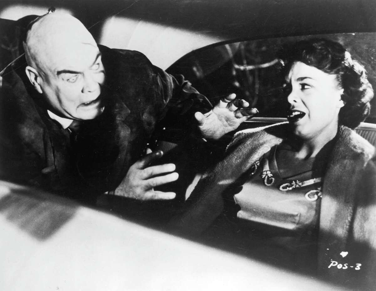 Swedish-born actor Tor Johnson attacks actor Mona McKinnon in the back seat of an automobile in a still from director Edward D. Wood Jr.'s film 'Plan 9 from Outer Space.' Johnson, who has a zombie expression, holds his hands outstretched.