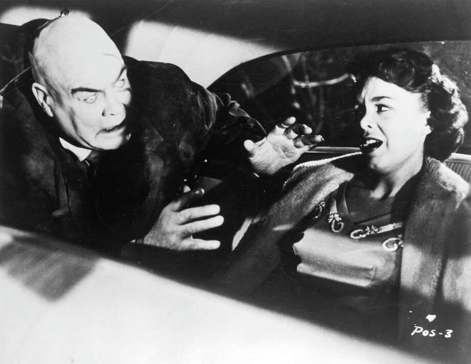 Swedish-born actor Tor Johnson attacks actor Mona McKinnon in the back seat of an automobile in a still from director Edward D. Wood Jr.'s film 'Plan 9 from Outer Space.'  Johnson, who has a zombie expression, holds his hands outstretched. Photo: Hulton Archive, Getty Images / Archive Photos