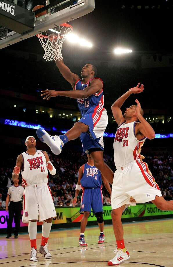 Dwight Howard (12) of the Eastern Conference goes to the basket over Carmelo Anthony (15) and Tim Duncan (21) of the Western Conference during the 57th NBA All-Star Game, part of 2008 NBA All-Star Weekend at the New Orleans Arena on Feb. 17, 2008 in New Orleans. Photo: Ronald Martinez, Getty Images / 2008 Getty Images