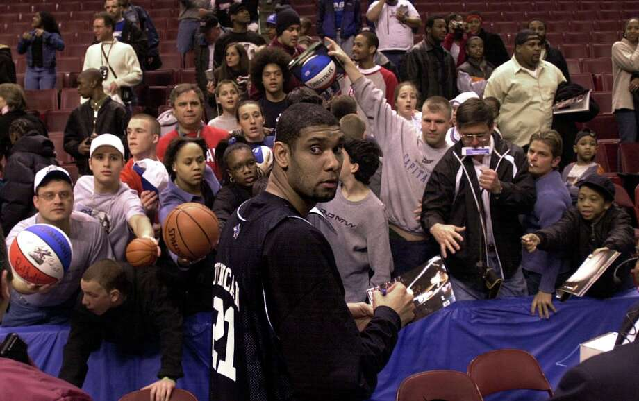 Spurs' All-Star forward Tim Duncan draws a crowd while signing autographs prior to a team practice at the Union Center in Philadelphia on Saturday, Feb. 9, 2002. Photo: KIN MAN HUI, SAN ANTONIO EXPRESS-NEWS / SAN ANTONIO EXPRESS-NEWS