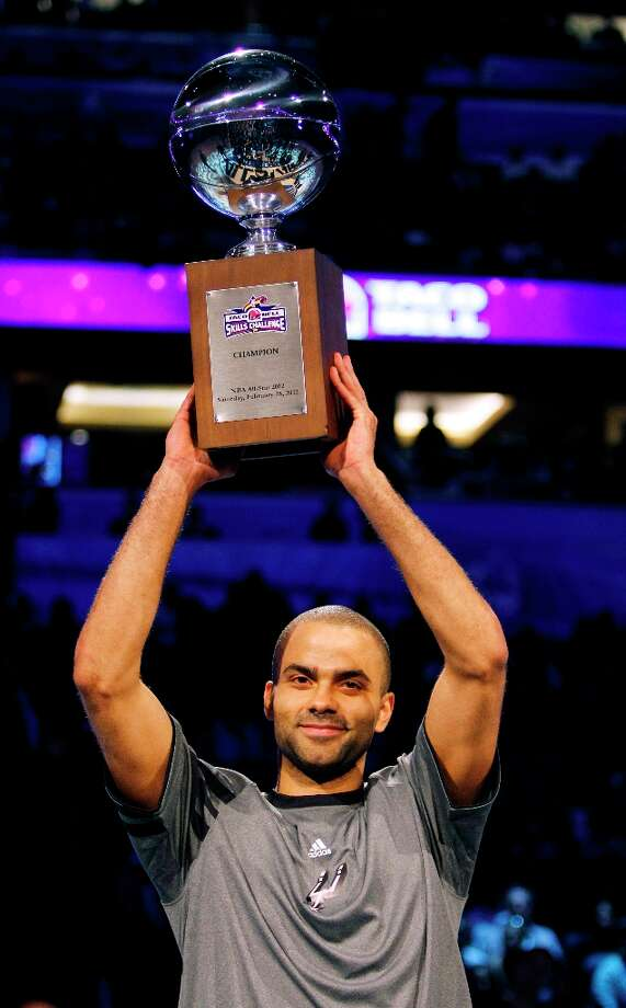 The Spurs' Tony Parker (9) holds the NBA All-Star Skills Challenge competition trophy after winning the event in Orlando, Feb. 25, 2012. Photo: Lynne Sladky, AP / AP