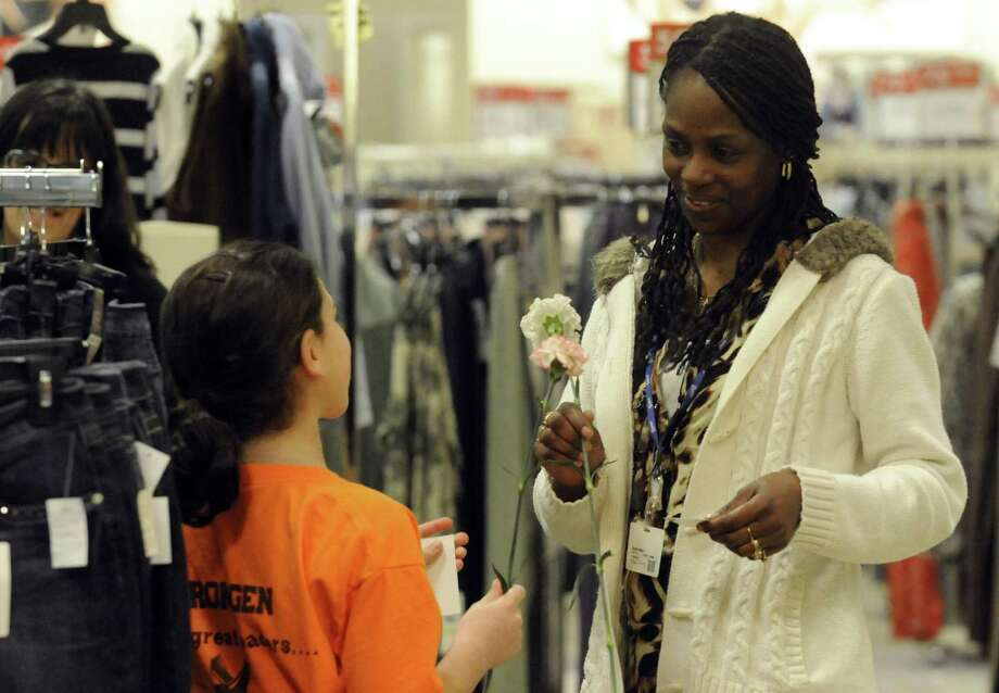 Arongen Elementary School fourth grade student Lauren Miller, left, gives a flower and a kindness card to Boscov's employee Telonia Downey at the Clifton Park Center Mall on Thursday Jan. 24,2013 in Clifton Park, N.Y. Arongen Elementary and the Arongen Student Council has begun an early celebration of Random Acts Of Kindness Week (Feb.11-17) by distributing ?Kindness Cards?. A ?Kindness Card? is given by a person to another person when they do a Random Act of Kindness for someone else. Their challenge is to distribute 10,000 Kindness Cards through our community and the capital district by the end of Random Acts of Kindness Week in February. (Michael P. Farrell/Times Union) Photo: Michael P. Farrell