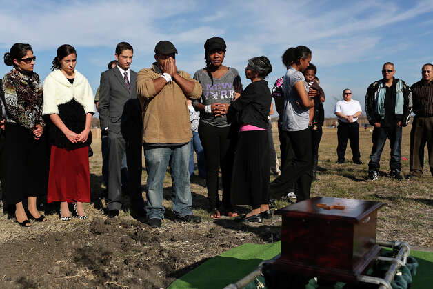 "Khristian Rohena and Shontae Minor, center, lay to rest their son, Yandel Rohena, one of their quadruplets born last week, during a burial service for Yandel in the ""Any Baby Can"" Garden at Chapel Hill Memorial Park cemetery in San Antonio on Thursday, Jan. 24, 2013. At right is Khristian's mother, Rosa Rohena, and Khristian's niece, Jordayn Gonzalez, right, carrying the couple's nine-month-old son Khristian Rohena, Jr. Photo: Lisa Krantz, San Antonio Express-News / © 2012 San Antonio Express-News"