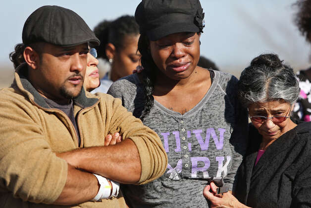 "Khristian Rohena, left, and Shontae Minor, center, grieve during the burial service for their son, Yandel Rohena, one of their quadruplets born last week, during a burial service for Yandel in the ""Any Baby Can"" Garden at Chapel Hill Memorial Park cemetery in San Antonio on Thursday, Jan. 24, 2013. At right is Khristian's mother, Rosa Rohena. Photo: Lisa Krantz, San Antonio Express-News / © 2012 San Antonio Express-News"