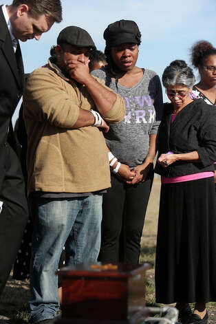 "Khristian Rohena, left, and Shontae Minor, center, lay to rest their son, Yandel Rohena, one of their quadruplets born last week, during a burial service for Yandel in the ""Any Baby Can"" Garden at Chapel Hill Memorial Park cemetery in San Antonio on Thursday, Jan. 24, 2013. At right is Khristian's mother and Yandel's grandmother, Rosa Rohena. Photo: Lisa Krantz, San Antonio Express-News / © 2012 San Antonio Express-News"